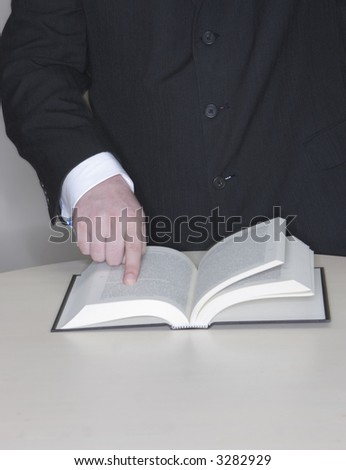 Businessman standing with his finger pointing at a place in an open book