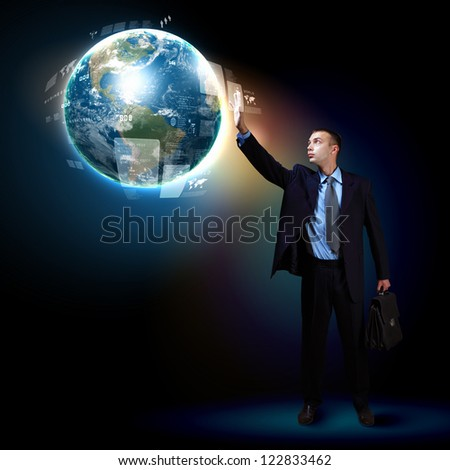 Businessman standing with modern technology symbols next to him. Elements of this image are furnished by NASA - stock photo