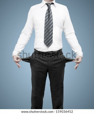 businessman standing with pockets turned inside out on blue background - stock photo