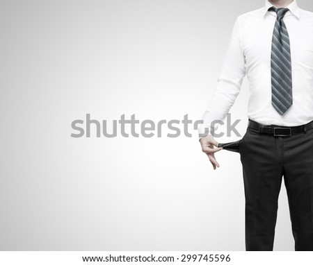 businessman standing with pockets turned inside out on gray background