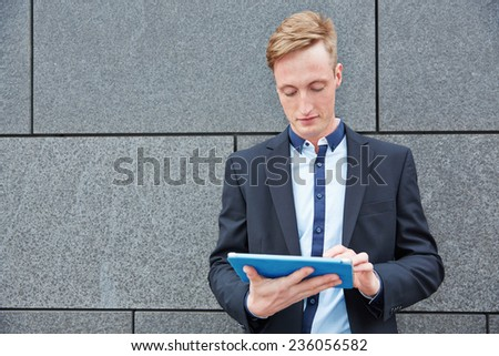 Businessman standing with tablet PC outside leaning on a wall - stock photo