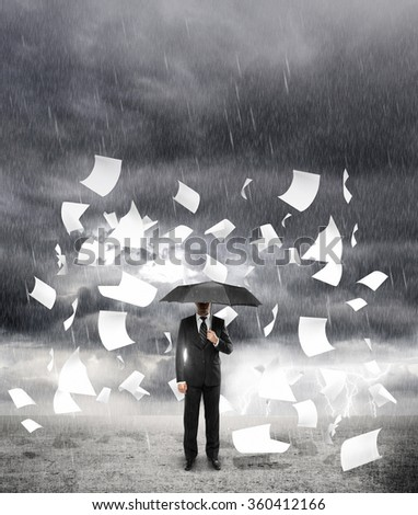 businessman standing with umbrella in rainy weather with flying around paper - stock photo