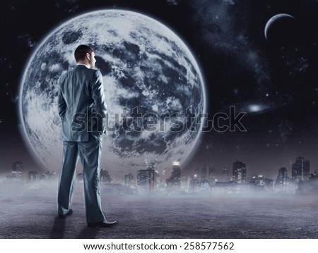 Businessman stands looking at the moon - stock photo