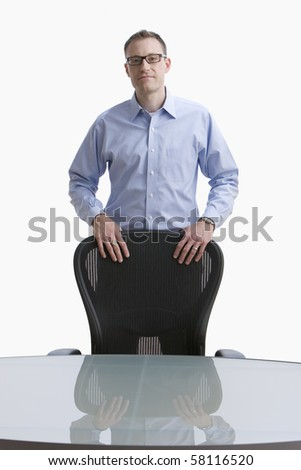 Businessman stands with his hands on a conference room chair.  Vertical shot.  Isolated on white. - stock photo