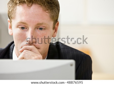 Businessman staring at computer - stock photo