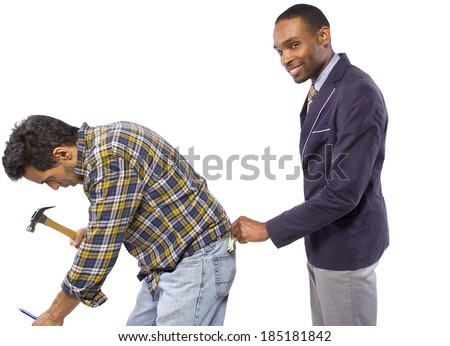 Businessman Stealing from a Blue Collar Worker - stock photo