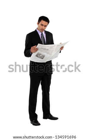 Businessman stood reading the newspaper - stock photo