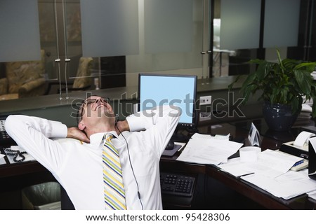 Businessman stretching at desk