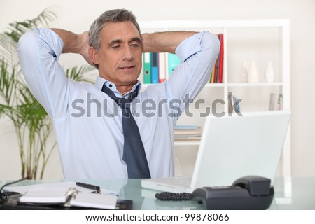 Businessman stretching at his desk - stock photo