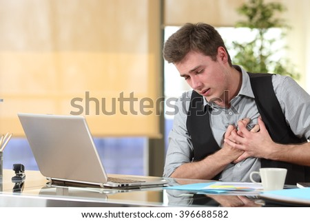 Businessman suffering a heart attack with his hands grabbing the chest sitting in a desktop at office - stock photo
