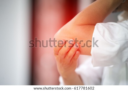 Businessman suffering from elbow pain at office