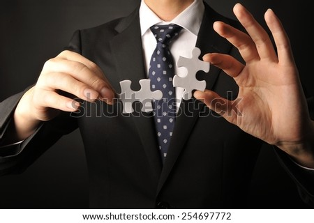 Businessman suffering to have a piece of jigsaw puzzle - stock photo