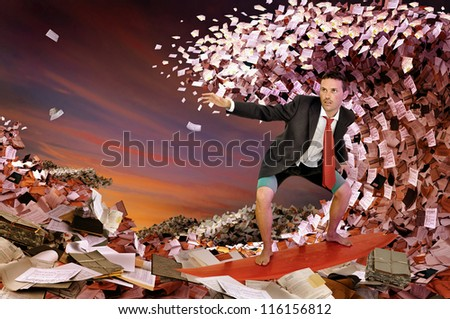 Businessman surfing in a sea made of files and papers - stock photo