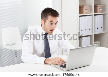 Businessman surprised looking at computer