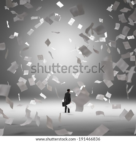 Businessman surrounded by blank flying papers - stock photo