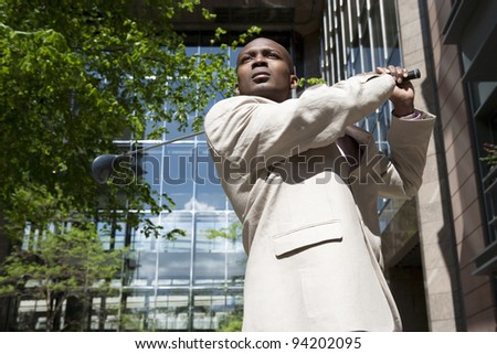Businessman swinging a golf club in the middle of the city. - stock photo