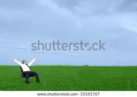 businessman take energy from nature in the meadow with dark blue sky - stock photo