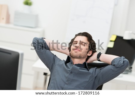 Businessman taking a break at his desk leaning back in his chair with closed eyes and his hands clasped behind his head
