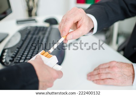 Businessman taking a cigarette at the office - stock photo