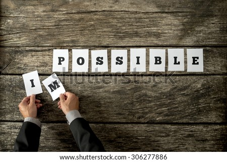 Businessman taking away letters IM from the word impossible changing it into possible spelled on individual white cards lying on cracked old wooden desk. Conceptual of positive attitude. - stock photo