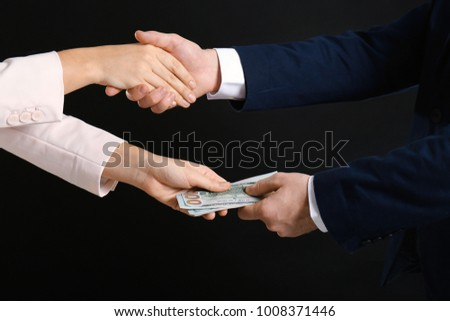 Businessman taking bribe from woman on black background