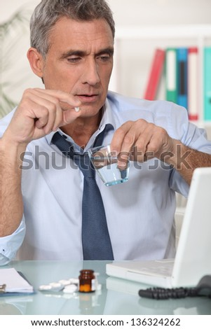 Businessman taking his medication - stock photo