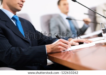 businessman taking notes, meeting businessmen at the table there are microphones and decomposition of business documents