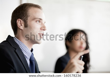 Businessman talking and gesturing at business meeting