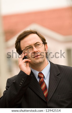 Businessman talking by mobile phone over blurred house background