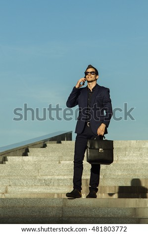 businessman talking on a mobile phone ,standing on a ladder in a business suit