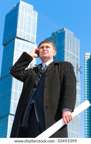 Businessman talking on cell phone and holding drawing in his hand,on skyscrapers background - stock photo