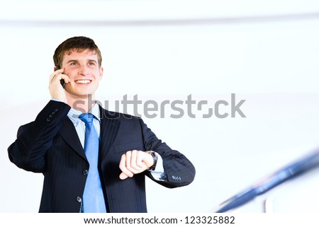 Businessman talking on cell phone and looking at his watch