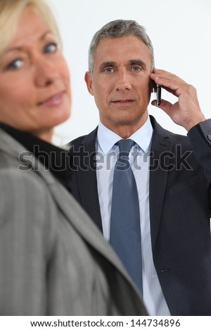 Businessman talking on his mobile phone beside his colleague - stock photo