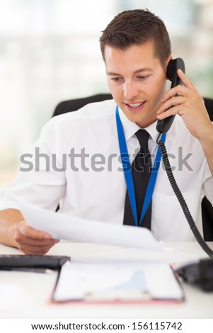 businessman talking on landline phone looking at business documents handheld - stock photo