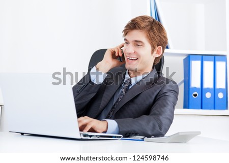 businessman talking on mobile phone using laptop, happy smile sitting at the desk in office talking cellphone, handsome young business man phone call, looking at computer screen - stock photo