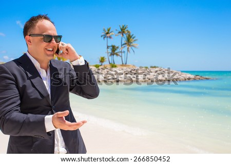 Businessman talking on phone at the beach - stock photo