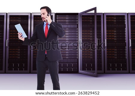 Businessman talking on phone holding tablet pc against server towers