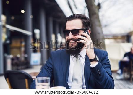 Businessman talking on smart phone at cafe bar. - stock photo