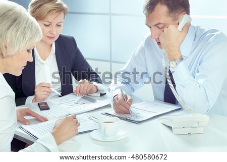 Businessman talking on telephone and writing on paper with two businesswomen working near by