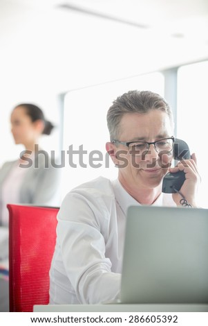 Businessman talking on telephone with colleague in background at office - stock photo