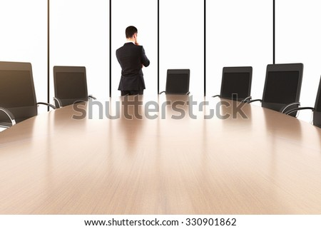 Businessman talking on the phone and conference table with chairs in the empty office 3D Render - stock photo