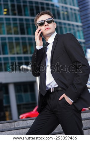 Businessman talking on the phone and holding his left hand in his pants pocket. - stock photo