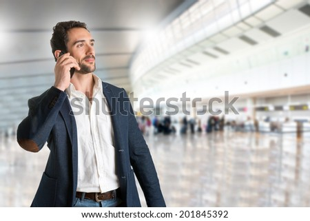 Businessman talking on the phone, in a airport - stock photo
