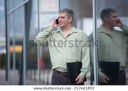 businessman talking on the phone, shiny building at the background - stock photo