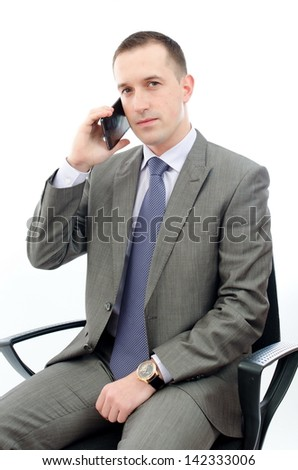 Businessman talking on the phone sitting in a chair in a bright office. - stock photo