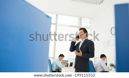 Businessman talking on the phone while his young colleagues are busy with work - stock photo