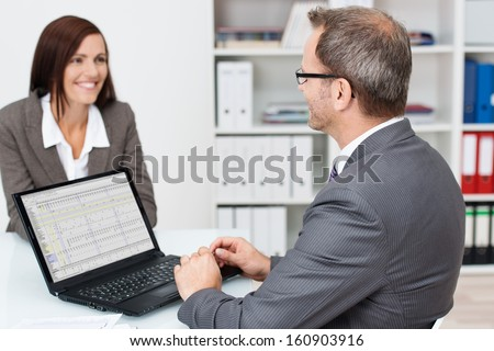 Businessman talking to a female colleague in the office as he sits at his desk working on his laptop computer - stock photo