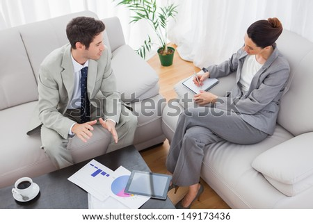 Businessman talking while colleague is taking notes sitting on sofa at office - stock photo