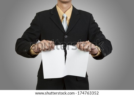 Businessman tear blank paper on gray background - stock photo