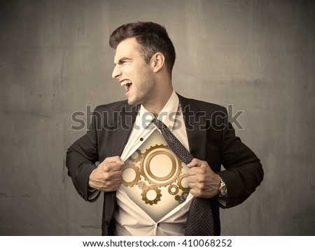 Businessman tearing shirt off and machine cog wheel shows on his chest concept on background - stock photo